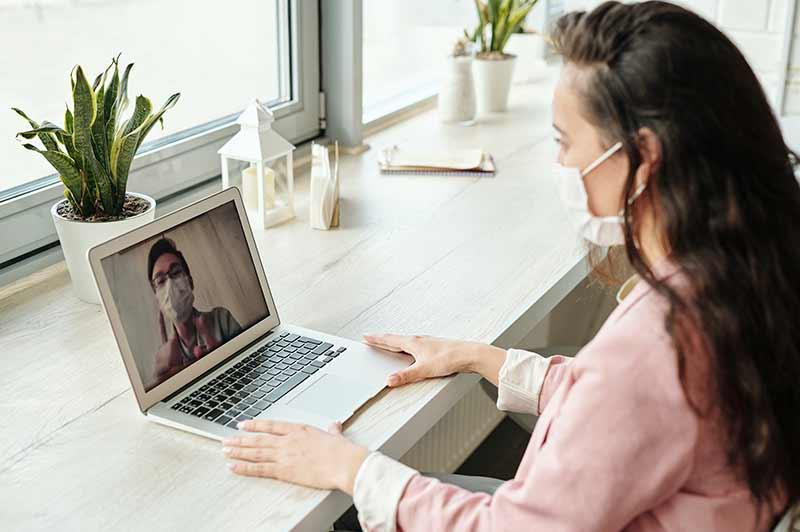 Locatiefoto (vrouw achter beeldscherm om aan te geven dat het een online event betreft)